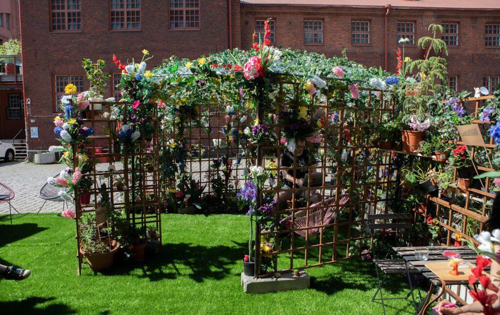 Puutarhassa sijaitseva paviljonki, joka on verhoiltu kukilla ja köynnöksillä.