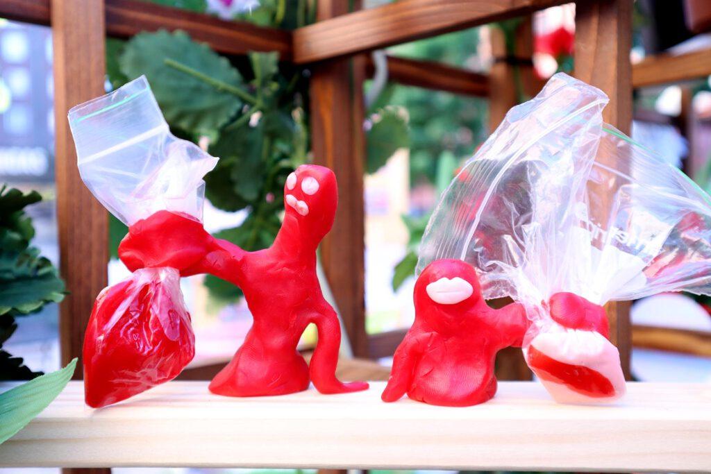 Queer AI: Puutarhan työpajassa muovailtu luomiskertomuksen omakuva. Kaksi punaista hahmoa, joilla vaaleanpunaiset kasvonpiirteet ja muovipussit käsissä.