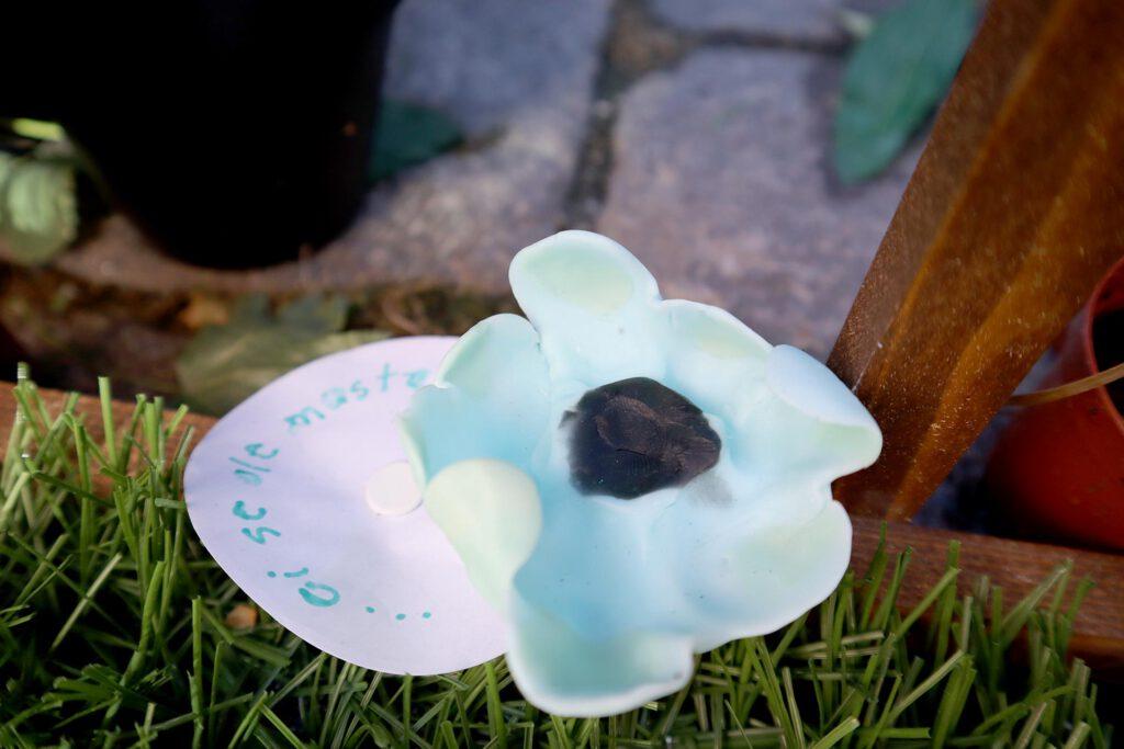 Queer AI: Puutarhan työpajassa muovailtu luomiskertomuksen omakuva. Sininen kukka, jolla musta keskusta.