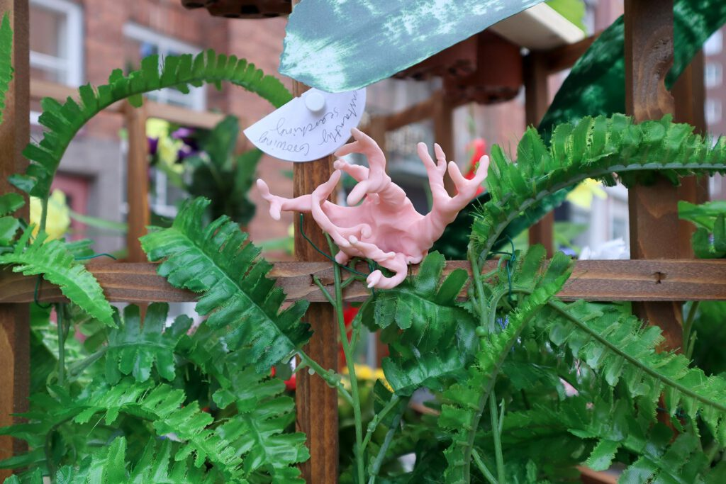 Queer AI: Puutarhan työpajassa muovailtu luomiskertomuksen omakuva. Vaaleanpunainen sarvisto.