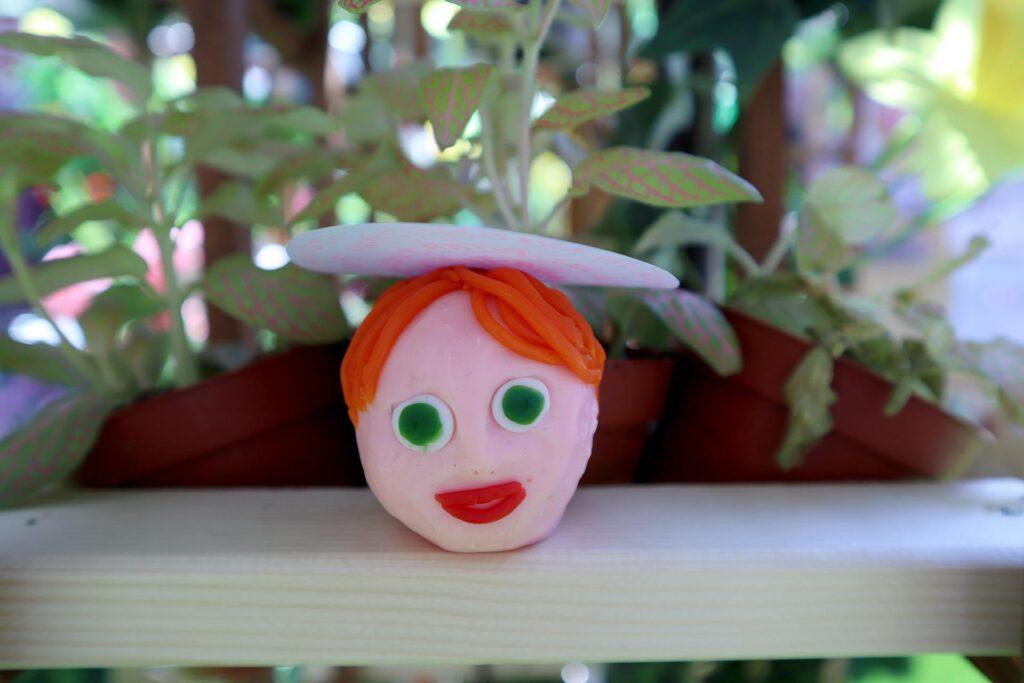 Queer AI: Puutarhan työpajassa muovailtu luomiskertomuksen omakuva. Oranssitukkainen ihmispää.