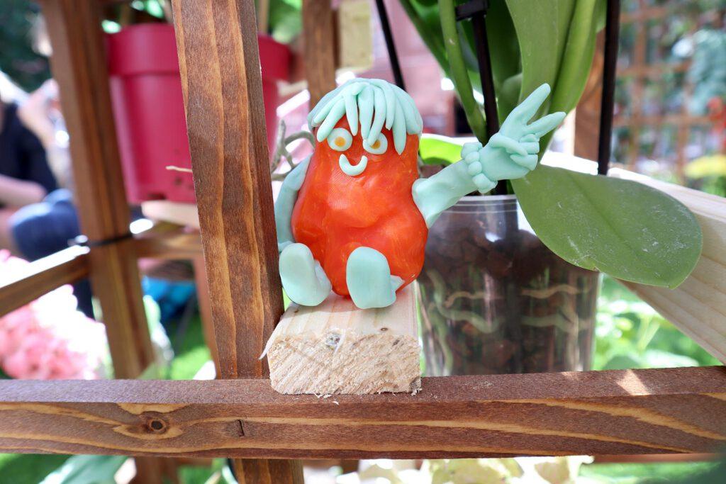 Queer AI: Puutarhan työpajassa muovailtu luomiskertomuksen omakuva. Oranssi hahmo.